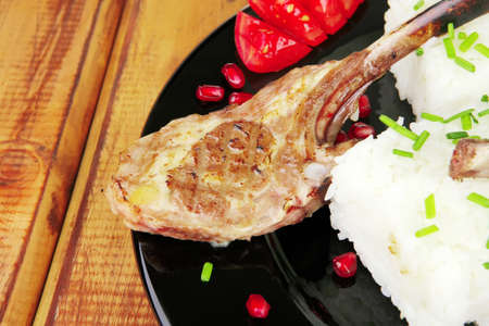 meat savory: roast veal ribs with rice garnish and pomegranate seeds on black over wood photo
