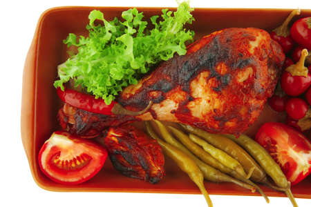chicken drumstick with tomato and green peppers on white photo