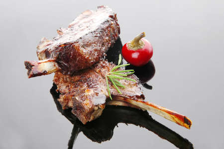 meat savory: roast ribs on black plate with red hot pepper Stock Photo - 9142920