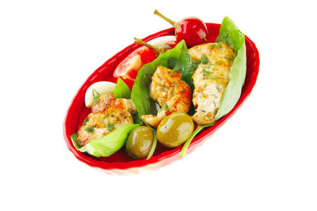 chicken pieces on red dish with tomatoes photo