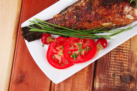 whole fried bass on plate over wood, served with lemons and tomatoes photo