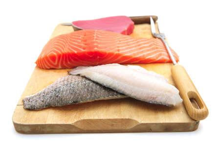 saumon cru frais, thon rouge et morceaux de poisson seul sur une planche de bois isolée sur fond blanc