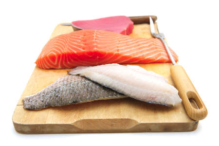 fresh raw salmon , red tuna , and sole fish pieces over wooden board isolated on white background