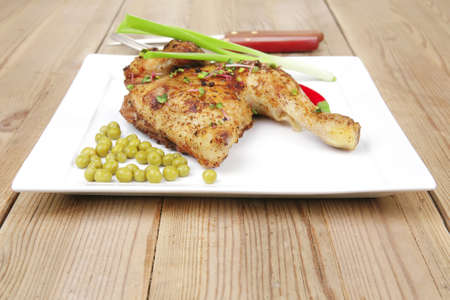 roast meat : roasted chicken legs garnished with green peas , peppers , and garlic on white plates over wooden table photo