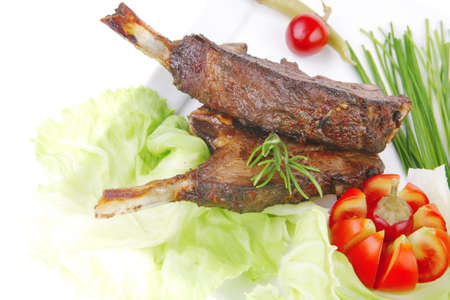 meat plate: roast ribs on white with tomatoes and red hot peppers isolated on white Stock Photo - 9336502