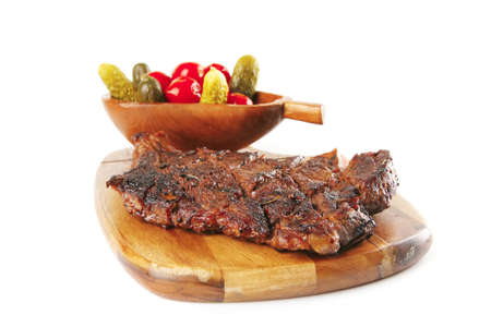 grilled meat on wooden plate with salty vegetables