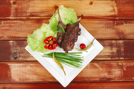 meat plate on wooden table: roast ribs on white with tomatoes and red hot peppers  photo