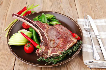 savory : grilled spare rib on dark dish with thyme pepper and tomato on wooden table Stock Photo - 9384719