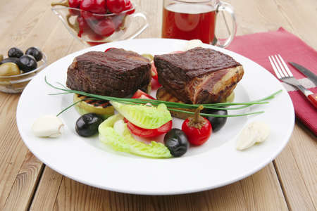 roast meat : beef (pork) steak garnished with baked apples , juice, green and black olives , tomatoes , on wooden table photo