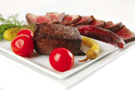 beef slices and vegetables on white plates . shallow dof photo
