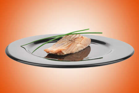 savory fish portion : norwegian salmon fillet roasted with green chinese onion, on black dish isolated over white background Stock Photo - 9435044