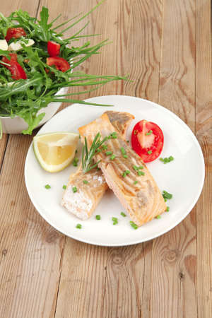 savory fish portion : roasted norwegian salmon chunks and vegetable salad on white dish over wooden table Stock Photo - 9476736