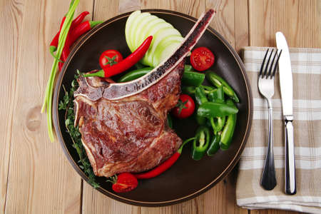 savory : roasted beef spare rib on dark dish with cutlery thyme pepper and tomato on wooden table Stock Photo - 9500606