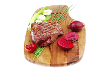 meat food : roast beef garnished with green lettuce and red chili hot pepper on wooden plate isolated over white background photo