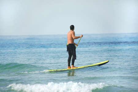 encrespado: hombre en paddleboard sobre el mar