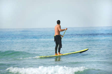 canoe paddle: man on paddleboard over sea