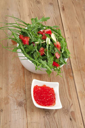 healthy food : green vegetable salad ( arugula with chives, tomatoes and olive oil) with red salmon caviar over wooden table photo