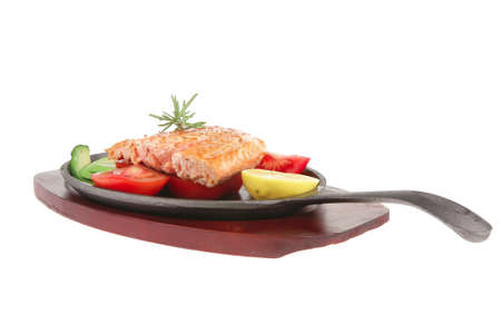 food: hot grilled salmon on metal pan over wooden plate isolated on white background photo