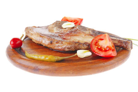fresh grilled beef meat fillet on red wooden plate with tomatoes and capers isolated over white background photo