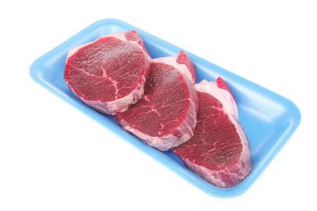 butchery : fresh raw beef lamb big fillet mignon ready to cooking on blue tray isolated over white background photo