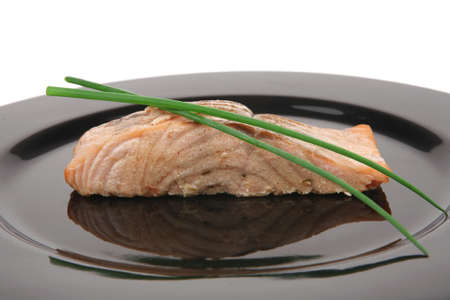 savory fish portion : norwegian salmon fillet roasted with green chinese onion, on black dish isolated over white background Stock Photo - 9624433