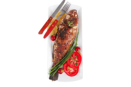sunfish: savory isolated on white: whole fried sunfish over plate with tomatoes lemons and peppers Stock Photo