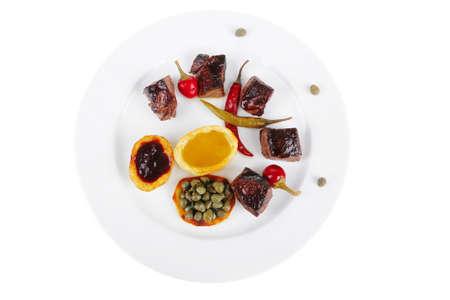 european food: alimentaria europea: Asado Goulache de carne de vacuno en Ronda plato blanco aislada sobre fondo blanco con rojo Aji, alcaparras y salsas