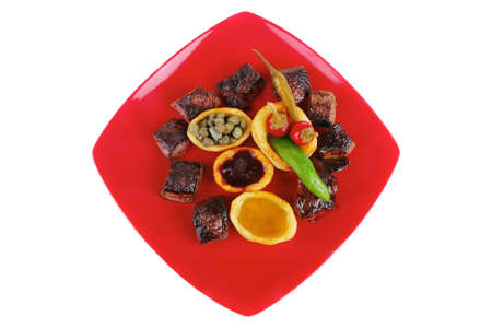 european food: alimentaria europea: a la gulash de carne en placa roja con chiles, alcaparras y aceitunas aceite y salsa de barbacoa Foto de archivo