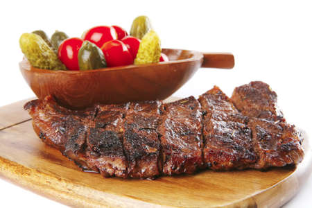 carne asada: carne a la parrilla en plato de madera con verduras saladas