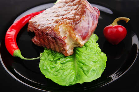 barbecued meat : beef ( lamb ) garnished with green lettuce and red chili hot pepper on black dish isolated over white background Stock Photo - 9776656