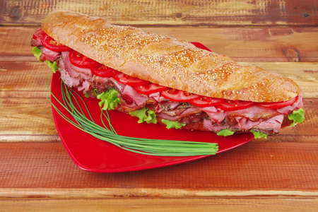 french sandwich on red plate : baguette with smoked sausage over wooden table photo