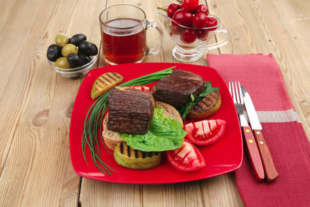 savory food : roast beef garnished with vegetables , juice and olives on red plate over wooden table Stock Photo - 9881370