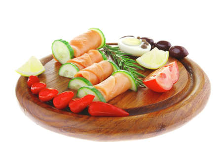 red smoked salmon slices with vegetables and lemon photo