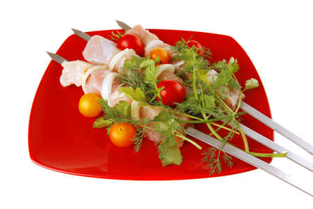 raw chicken kebabs on red served with tomatoes photo