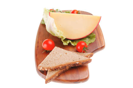 cheese and vegetables served on wooden plate photo