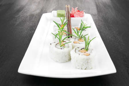 Maki Sushi - California Roll made of Smoked salmon, Cream Cheese and Deep Fried Vegetables inside. With wasabi and ginger. on black table photo