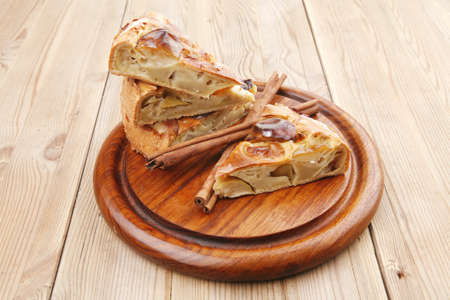 baked food : apple pies on wooden plate over table with cinnamon sticks photo