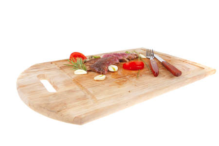 fresh roasted lamb meat fillet ready on wooden board with cutlery isolated  over white background photo
