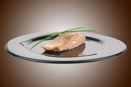 savory fish portion : norwegian salmon fillet roasted with green chinese onion, on black dish isolated over white background Stock Photo - 9928682