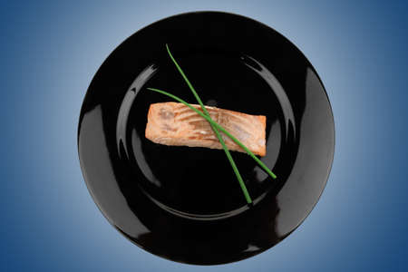 savory fish portion : norwegian salmon fillet roasted with green chinese onion, on black dish isolated over white background Stock Photo - 9927707