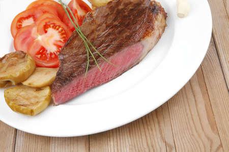 rib: Carne: arrosto di filetto mignon di manzo servito su piatto bianco con pomodori, patate e erba cipollina su tavola di legno
