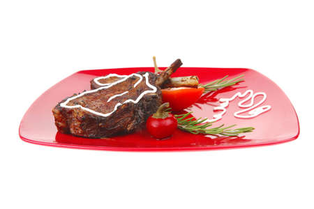 meat savory: roast ribs on red plate with peppers and rosemary photo