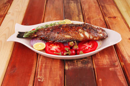 main course: whole fried seabass served on wood with lemons,tomatoes and peppers Stock Photo - 9991791
