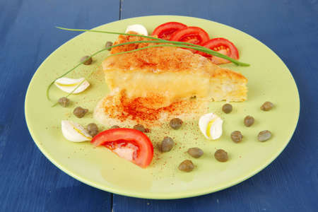 dairy food : vegetable cheese casserole slice on green plate served prepared with tomatoes  and garlic on blue table photo