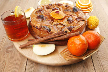 sweet apple cake served with apples lemon mandarin and tea cup on wooden plate over table photo
