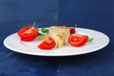 food : cheese casserole piece on white plate served with parsley and tomatoes on blue table photo
