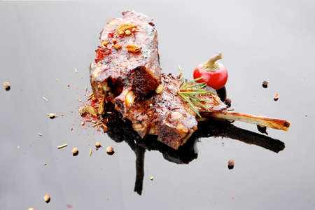 meat savory: roast ribs on black plate with red hot pepper photo