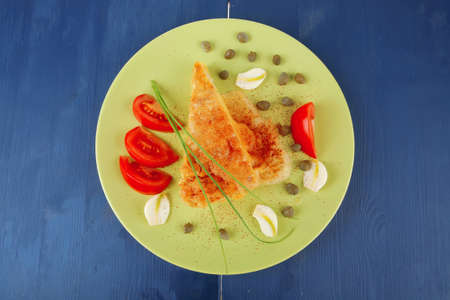 dairy food : cheese casserole piece on light green plate tomatoes , chives , and garlic on blue table photo