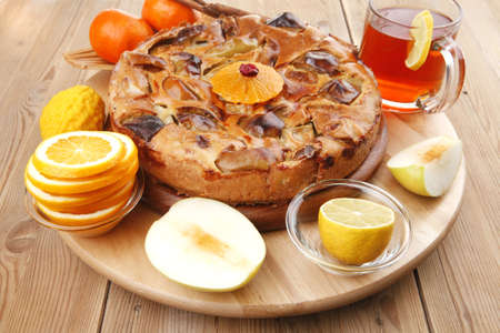 baked food : big apple pie served with fresh apples, raw lemon and mandarin,  tea cup on wooden plate over table photo