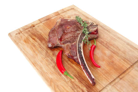 savory : roasted beef spare rib on wooden plate with cutlery and thyme isolated over white background photo